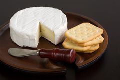 Brie and Crackers. Brie and butter cracker on a wooden cheese plate with cheese knife Royalty Free Stock Photo