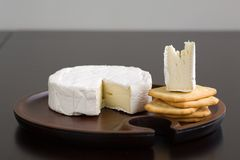 Brie and Crackers. Brie and butter cracker on a wooden cheese plate with cheese knife Royalty Free Stock Photos