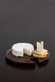 Brie and Crackers. Brie and butter cracker on a wooden cheese plate with cheese knife Stock Image