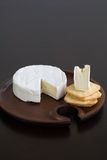 Brie and Crackers. Brie and butter cracker on a wooden cheese plate with cheese knife Stock Photography