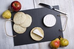 Brie de famille cheese and small round loaves lie on a slate Board on a white wooden background, round cheese, sliced cheese on stock photography