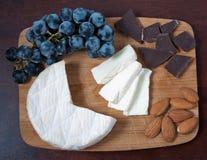 Brie, druvor, choklad och mandlar på ett träbräde royaltyfria foton