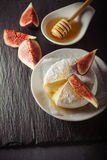 Brie with Figs. A wheel of melted brie covered in sliced figs and honey  on a stone plate Royalty Free Stock Photo