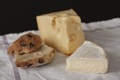 Brie francese e formaggio svizzero dell'emmental con le fette di salsiccia del salame e di panino al forno domestico disposto su  immagini stock