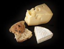 Brie francese e formaggio svizzero dell'emmental con le fette di salsiccia del salame e di panino al forno domestico su fondo ner immagini stock libere da diritti