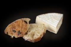 Brie francese e un panino al forno domestico su fondo nero immagini stock