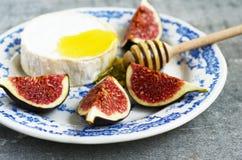 Brie, Honig und Feige auf blauer keramischer Platte Stockbild