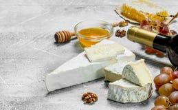 Brie mit Honig, Trauben und Weißwein stockbild