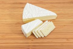 Brie parzialmente affettato sul tagliere di legno immagini stock