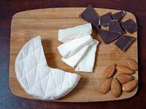 Brie, Schokolade und Mandeln auf einem hölzernen Brett Lizenzfreies Stockfoto