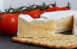 Brie soft cheese with crackers and  tomato  on a grey slate boar. D.  Selective Focus Stock Images