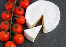 Brie soft cheese with tomato on a grey slate board. Brie soft cheese with tomato spray on a grey slate board. Selective Focus Royalty Free Stock Photo