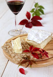 Brie, soft French  cow's milk cheese, autumn leaves and a winegl Stock Photos