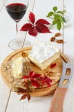 Brie, soft French  cow's milk cheese, autumn leaves and a winegl Royalty Free Stock Image