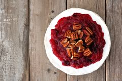 Brie topped with cranberries and pecans, above on wood Stock Photography