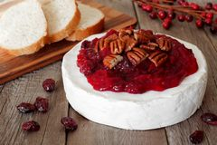 Brie topped with cranberry sauce and pecans on rustic wood Royalty Free Stock Photo