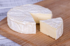 Brie type of cheese. Camembert cheese. Fresh Brie cheese and a slice on a wooden board. Italian, French cheese. Stock Image