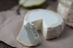 Piece smelly camembert cheese on a wooden rustic table. Brie type of cheese. Camembert cheese. Fresh Brie cheese and a slice on a wooden board with pear and stock images