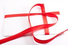 Brief die met een rood lint in de vorm van hart wordt gebonden stock foto