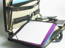 Briefcase. Over flowing case with diary, planner, and files over spilling Stock Images