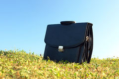 Briefcase. Black business briefcase in the grass field over clear blue sky stock images