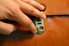 Briefcase. A hand on a brassy clasp of a brown briefcase stock photo