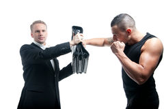 Briefcase defense. A young businessmen defending a punch with his briefcase stock images