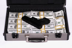 Briefcase full of cash and pistol Royalty Free Stock Photos