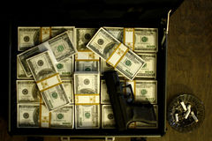Briefcase full of cash and pistol Royalty Free Stock Photo
