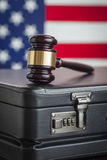 Briefcase and Gavel Resting on Table with American Flag Behind. Leather Briefcase and Gavel Resting on Table with American Flag Behind Royalty Free Stock Photos