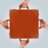 Briefcase hands. Business teamwork concept showing multiple hands holding a briefcase stock images