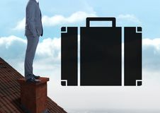 Briefcase icon next to Businessman standing on Roof with chimney and cloudy sky. Digital composite of Briefcase icon next to Businessman standing on Roof with Royalty Free Stock Photo