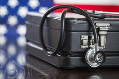 Briefcase and Stethoscope Resting on Table with American Flag Be Stock Photos