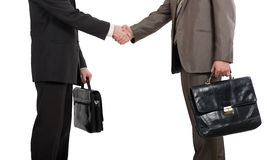 Briefcases and shaking hands. Two businessmen holding briefcases and shaking hands over white background Stock Image