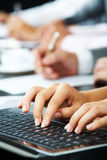 At briefing. Photo of female�s hands touching keys of laptop during briefing on background of human hands Stock Photo