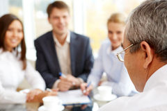 During briefing. Rear view of boss looking at subordinate persons during briefing Royalty Free Stock Image