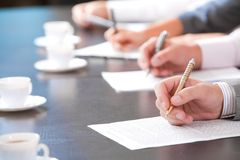 At briefing. Close-up of masculine hand holding ballpoint over business document on background of human hands with cups of coffee near by stock photo