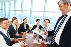 Briefing. Smart and confident boss looking at managers with papers at meeting stock photos