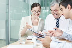 Briefing. Three businesspeople holding discussion in office stock images