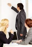 Briefing. A business men drawing a plan on a whiteboard for his colleagues stock photo