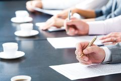 At briefing. Close-up of masculine hand holding ballpoint over business document on background of human hands with cups of coffee near by royalty free stock photography