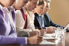 Briefing. Row of businesspeople writing review of their work with senior boss at background Royalty Free Stock Image
