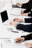 At briefing. Image of row of people hands writing on papers and typing at briefing Royalty Free Stock Images