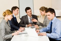 Briefing. Portrait of confident colleagues working while confident woman sharing her idea with co-workers on background royalty free stock image