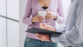 Briefing during a coffee break. Business people having a briefing during a coffee break, a woman is holding a cup of coffee, her collegue is holding a clipboard Stock Photography