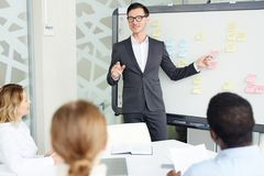 Briefing of colleagues. Elegant businessman pointing at whiteboard and explaining new business trends to colleagues at briefing Royalty Free Stock Photography