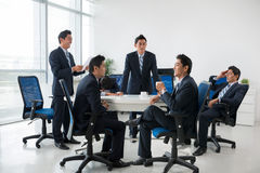 Briefing. Composite image of entrepreneur having business meeting with his clones stock image
