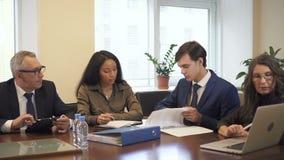 Briefing dans la salle de conférence confortable de bureau de société multi-ethnique banque de vidéos