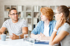 Briefing for managers. Group of three young people interacting at briefing Royalty Free Stock Photo