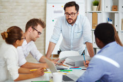 Briefing. Young Asian businessman looking at colleagues at briefing Royalty Free Stock Photo